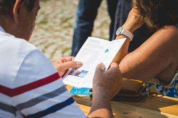 Ein Mann betrachtet das Faltblatt zum Flurbereinigungsverfahren Bollstedt-Dorf