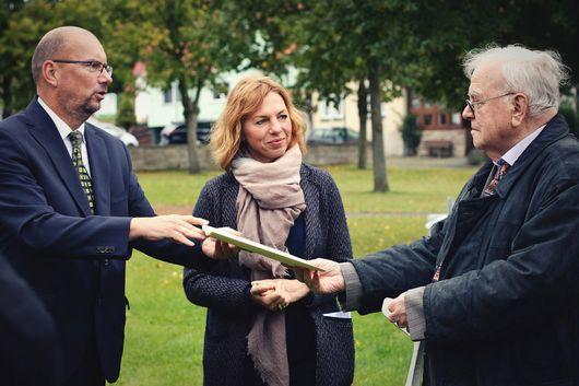 Präsident Uwe Köhler und Staatssekretärin Susanna Karawanskij überreichen dem Vorsitzendem der Teilnehmergemeinschaft, Werner Genzel, die Schlussfeststellung