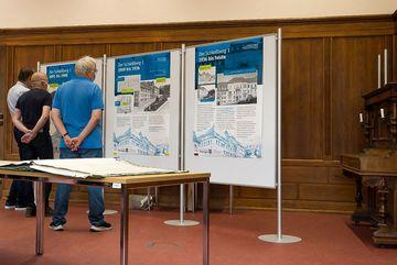 Besucher stehen vor den 3 Plakaten zur Ausstellung