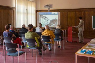 Herr Löffelholz begrüßt die Gäste im Saal mit einer Präsentation