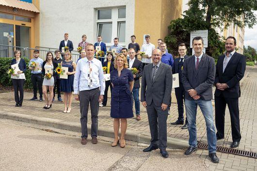 1. Reihe v. rechts: Andreas Püls (TLBG), ÖbVI Torsten Hentschel (Vorsitzender des BDVI Thüringen), Präsident Uwe Köhler (TLBG), Staatssekretärin Susanna Karawanskij (TMIL) und Frank Teichmann (TLBG) stehen vorm TLBG. In den Reihen dahinter: ehemalige Auszubildende mit ihren Zeugnissen.
