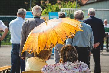 Zwei Damen mit Sonnenschirm im Publikum