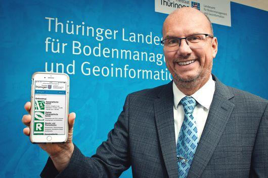 Präsident Uwe Köhler präsentiert den neuen Online-Shop auf einem Smartphone