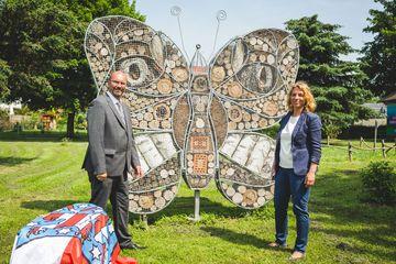 Präsident Uwe Köhler und Staatssekretärin Susanna Karawanskij vor einem Insektenhotel in Form eines Schmetterlings